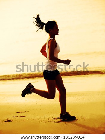 healthy lifestyle fitness woman jogging at sunrise/sunset beach - stock photo