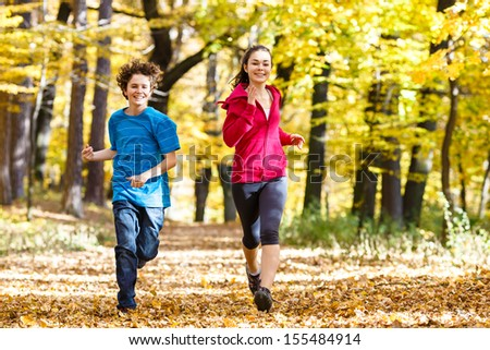 Healthy lifestyle - girl and boy running, jumping outdoor  - stock photo