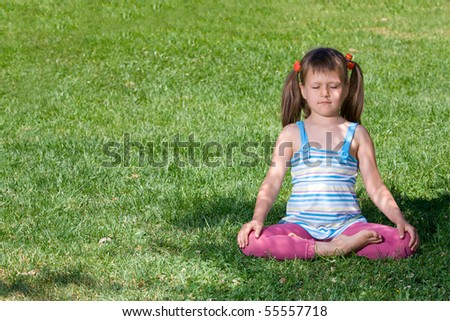 Healthy lifestyle. Little cute girl who is sitting and meditating in asana under tree shadow with closed eyes on the green grass - stock photo