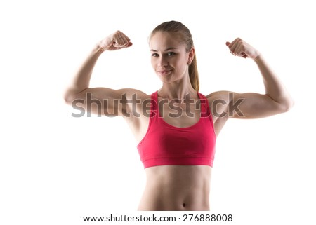 Healthy lifestyle: portrait of sporty young woman showing biceps muscles, studio shot, white background, isolated