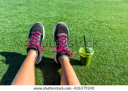 Healthy lifestyle runner girl running shoes selfie with green smoothie. Fitness woman drinking juice to go after workout in park. Healthy lifestyle sporty female athlete POV mobile phone feet picture. - stock photo