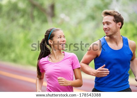 Healthy lifestyle - Running fitness couple jogging laughing, talking outside on road in beautiful nature. Multiracial sports couple, Asian woman model and man fitness model exercising smiling happy. - stock photo