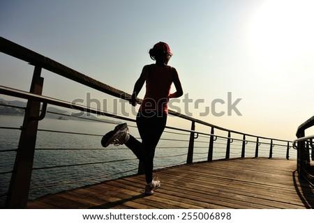 healthy lifestyle sports woman running on wooden boardwalk sunrise seaside  - stock photo