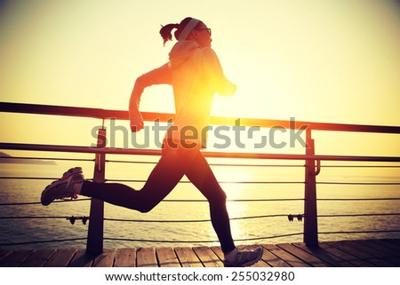 healthy lifestyle sports woman running on wooden boardwalk sunrise seaside  - stock photo