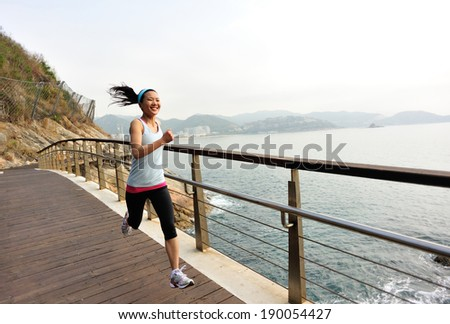 healthy lifestyle sports woman running on wooden bridge seaside