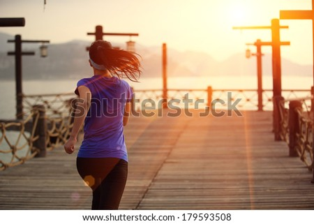 healthy lifestyle sports woman running on wooden pier  - stock photo
