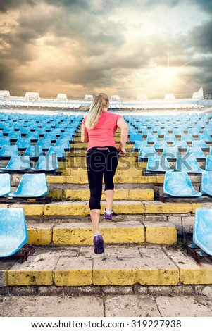 Healthy lifestyle sports woman running up on rock stairs stadium - stock photo