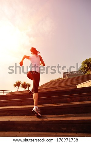 healthy lifestyle sports woman running up on wooden stairs  - stock photo