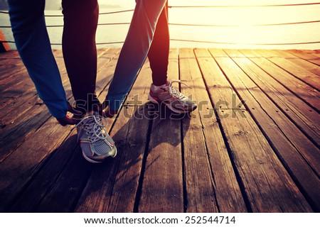 healthy lifestyle sports woman tying shoelace on wooden boardwalk sunrise seaside  - stock photo