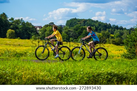 Healthy lifestyle - teenage girl and boy biking - stock photo