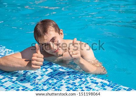 Healthy lifestyle. The young man is swimming in a pool on a sunny day