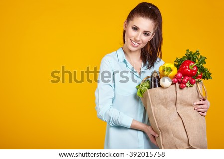 healthy lifestyle with green vegan food. young woman hold shopping bag with vegetables.