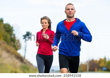 Healthy lifestyle - woman and man running - stock photo