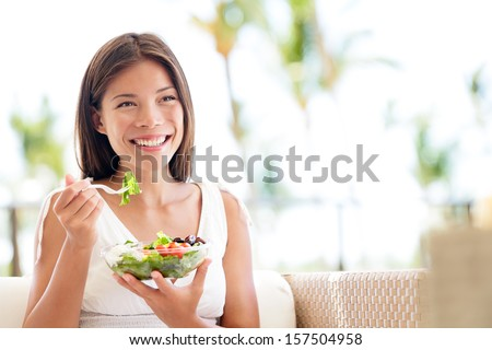 Healthy lifestyle woman eating salad smiling happy outdoors on beautiful day. Young female eating healthy food outside in summer dress laughing and relaxing in sofa. Pretty multiracial model. - stock photo