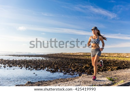 Healthy lifestyle woman runner running outside on summer nature trail by ocean beach. Happy Asian athlete training cardio and endurance outdoors. Motivation and wellness, active living. - stock photo