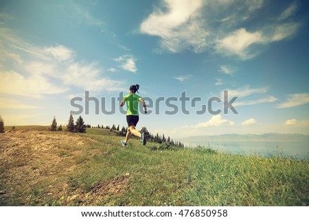 healthy lifestyle woman trail runner running on beautiful mountain peak