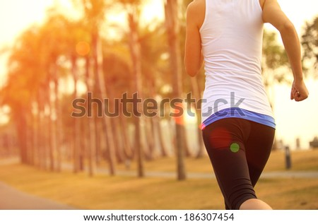 healthy lifestyle young asian sporty woman jogging at tropical park  - stock photo