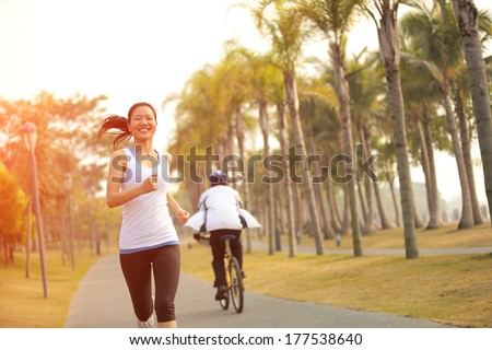 healthy lifestyle young asian woman running at tropical park  - stock photo