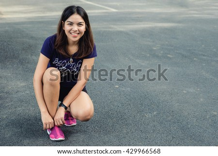 healthy lifestyle - Young happy woman in running road, sitting relax ready to jogging run, chubby asian woman running to get lost weight at park, sitting prepare shoes - stock photo