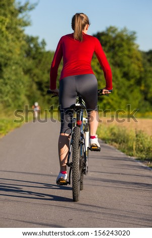 Healthy lifestyle - young woman biking  - stock photo