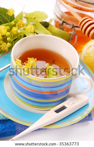 healthy linden tea in blue cup with honey and lemon - stock photo
