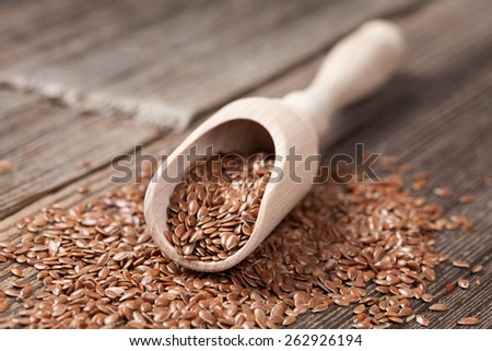 Healthy little brown flax seeds super foods  in wooden spoon. Organic vegetarian nutrition. - stock photo