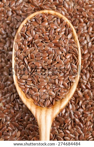 Healthy little brown flax seeds super foods  in wooden spoon. Organic vegetarian super food. - stock photo