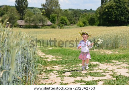 Healthy little girl walking with bunch of flowers near wheat field in summer