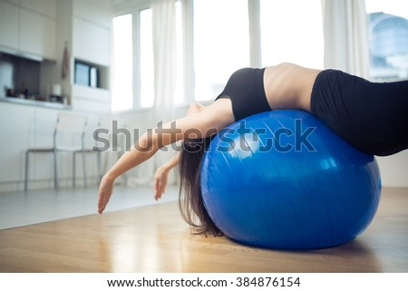 Healthy living fit woman using fitness pilates ball for exercise workout.After work relaxation and stretching every day routine in small improvised home space.Short exercises to do at home.Bridge - stock photo