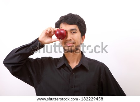 Healthy living. Man holding a red apple wearing a blue shirt. White background