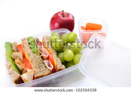 Healthy living packed lunch with sandwich, apple and carrots - stock photo