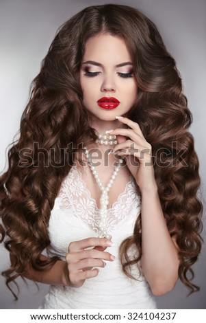 Healthy long hair. Beauty Portrait of a beautiful fashion girl with sensual red lips. Wedding make up and waving hairstyle. Luxury bride modern style.
