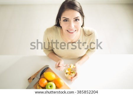 Healthy looking cheerful woman eating homemade organic fruit mix fruit salad.Fruit diet,dieting,nutrition,vegetarian concept.Food for better skin,strong immune system,diet fitness meal.Healthy snack - stock photo