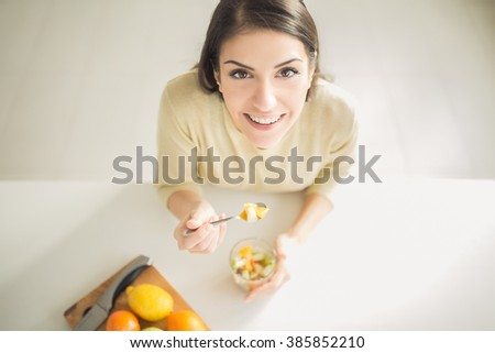 Healthy looking cheerful woman eating homemade organic fruit mix fruit salad.Fruit diet,dieting,nutrition,vegetarian concept.Food for beautiful skin,strong immune system,diet fitness meal.Heathy snack - stock photo
