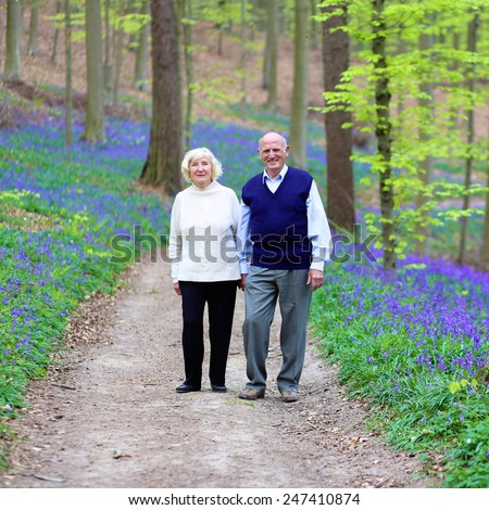 Healthy loving senior couple relaxing in beautiful summer forest full of fresh blooming bluebells or wild blue hyacinth flowers - active retirement concept - stock photo