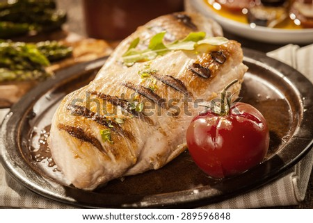 Healthy low fat grilled chicken breasts seasoned with fresh herbs and served with fresh tomato on a rustic metal plate - stock photo