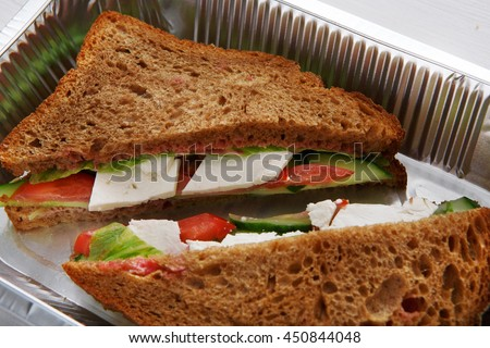 Healthy lunch and diet concept. Take away of fitness food. Weight loss nutrition in foil boxes. Sandwiches with whole-grain bread, cucumber, feta cheese and tomatoes at white wood, closeup - stock photo