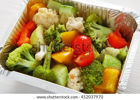 Healthy lunch and diet concept. Take away of fitness food. Weight loss nutrition in foil boxes. Boiled vegetables such as cauliflower, broccoli, cherry tomatoes and peppers at white wood, closeup - stock photo