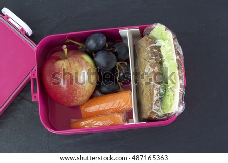 Healthy lunch box, cheese sandwich, apple, carrots and grapes. Topview image.