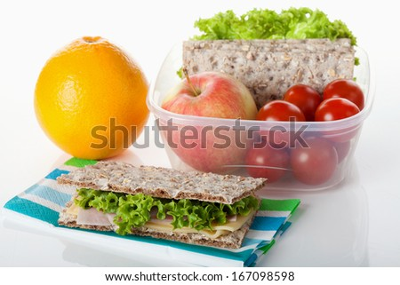 Healthy lunch box filled with fresh fruits, vegetables and crispbread - stock photo