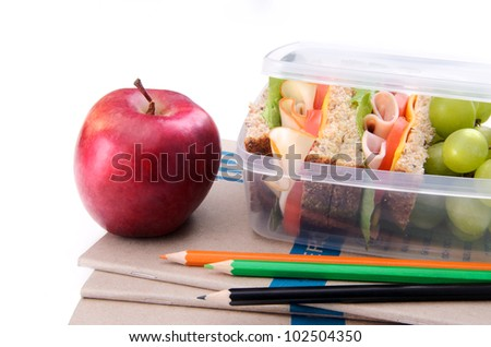 Healthy lunch box with sandwich and apple on books and pencils - stock photo
