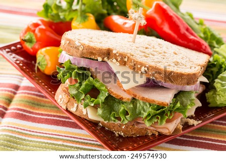 Healthy lunch food sandwich with turkey and ham on a plate with sweet peppers and lettuce - stock photo