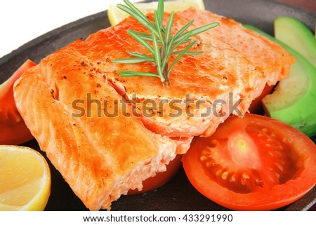 healthy lunch : sea roast salmon on metal pan over red wooden plate with vegetables isolated over white background - stock photo
