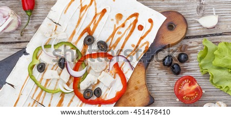Healthy lunch snack. Disclosed Tortilla wraps  with grilled chicken fillet and fresh vegetables on wooden background. Top view - stock photo