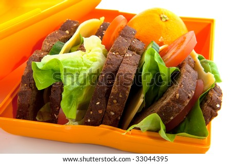 Healthy lunchbox filled with whole meal bread cheese and fruit - stock photo