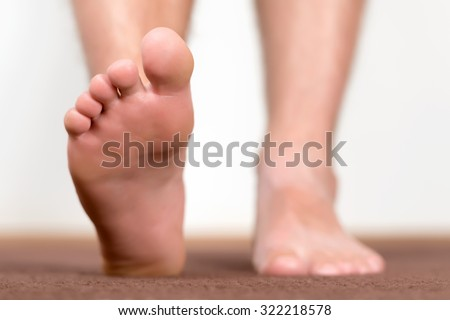 Healthy male feet stepping over home-like background. - stock photo