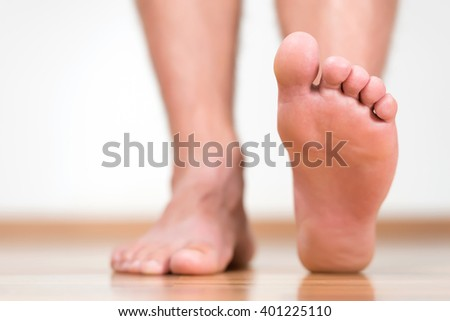 Healthy male feet stepping over home-like background