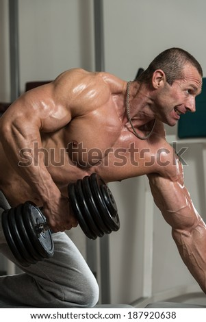Healthy Man Doing Back Exercises In The Gym With Dumbbell