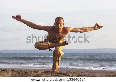 Healthy man exercising yoga with rising hands on coastline - stock photo