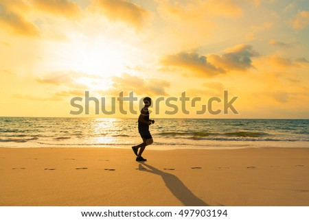 Healthy man jogging on Phuket beach in morning,Thailand